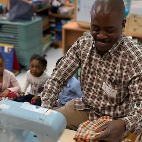 Dad demonstrates sewing for preschool students.