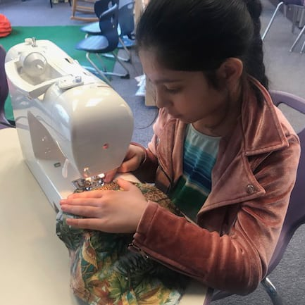 Clark student sewing a wildlife rescue pouch